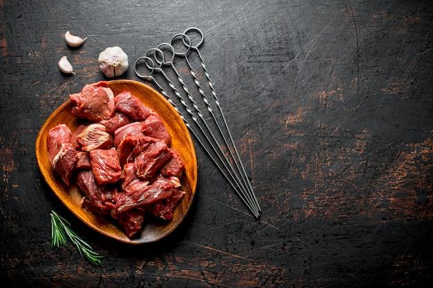 Kebab z surowej wołowiny na talerzu ze szaszłykami, czosnkiem i rozmarynem. na ciemnej rustykalnej powierzchni