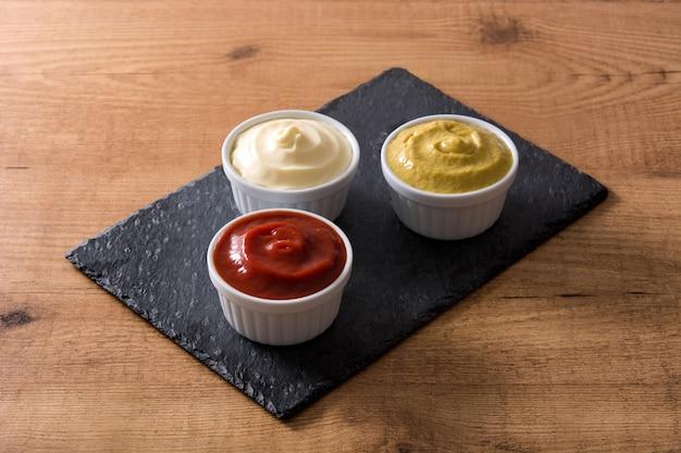 Keczup, musztarda i majonez w miskach na czarnym łupku