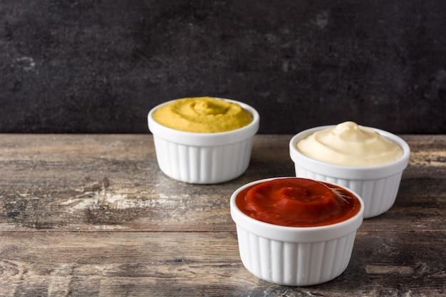 Keczup, musztarda i majonez w miskach na drewnianym stole kopiować miejsca