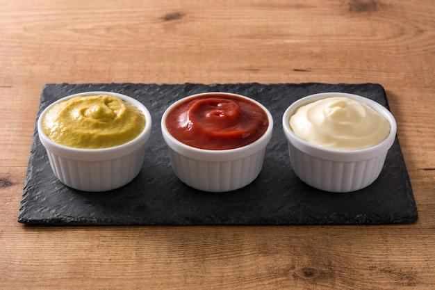 Keczup, musztarda i majonez w miskach na drewnianym stole