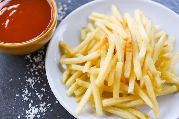Keczup z frytkami na białym talerzu i sól - smaczne frytki ziemniaczane do jedzenia lub przekąski pyszne włoskie menu domowe składniki