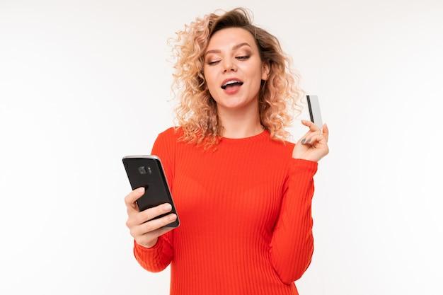 Kędzierzawa atrakcyjna dziewczyna z telefonem i kredytową kartą przeciw białemu studiu