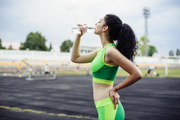 Kędzierzawa brunetka bawić się sporty na stadium. dziewczyna pije wodę z butelki