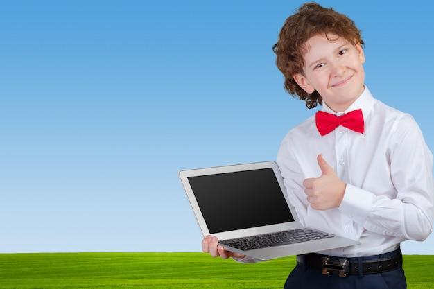 Kędzierzawa chłopiec w formalnym kostiumu z laptopem