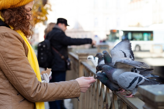 Kędzierzawa dziewczyna karmi gołębie chlebem. koncepcja wypoczynku i rekreacji