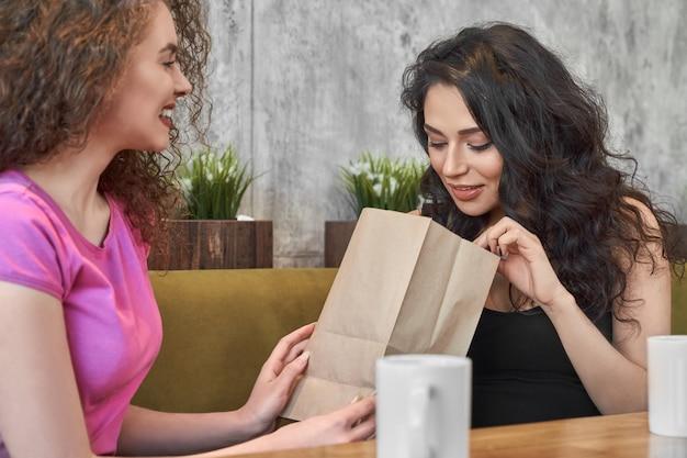 Kędzierzawa dziewczyna śmia się i robi prezentowi dla przyjaciela w pizzerii