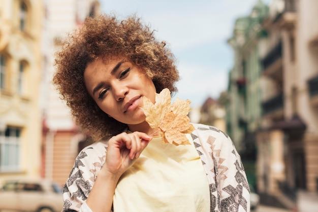 Kędzierzawa kobieta pozuje z liściem
