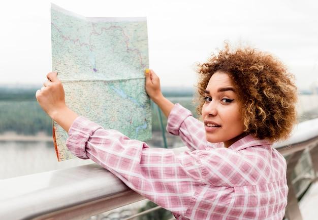 Kędzierzawa kobieta sprawdza mapę