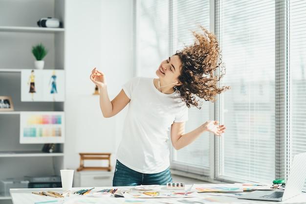 Kędzierzawa kobieta tańcząca przy stole ze sprzętem artystycznym