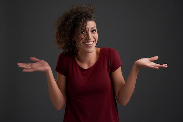 Kędzierzawa kobieta wzrusza ramionami przy kamerą przeciw zmrokowi - szarość