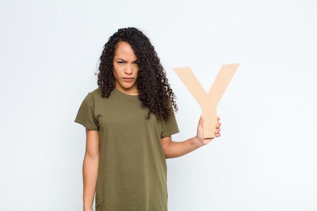 Kędzierzawa młoda kobieta trzyma literę y