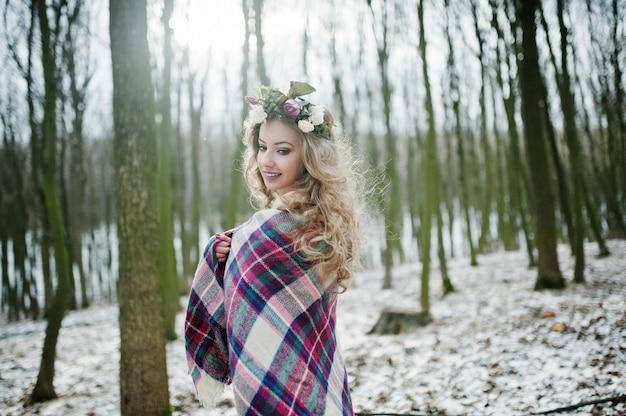 Kędzierzawa śliczna blondynki dziewczyna z wiankiem ww kratkę szkocką kratę przy śnieżnym lasem w zima dniu.