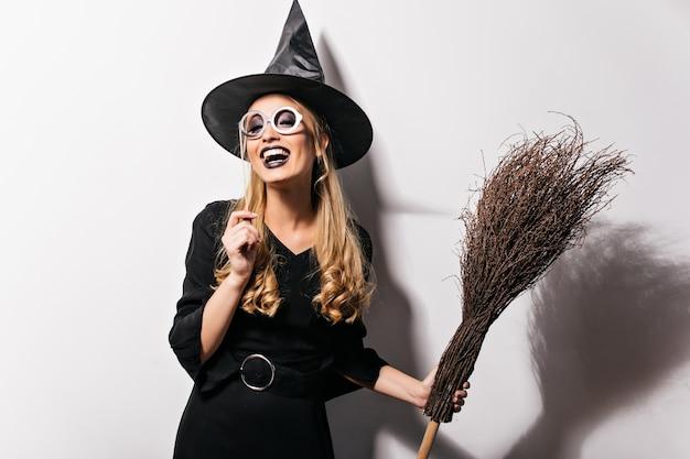 Kędzierzawa wiedźma w okularach wyrażająca szczęście w halloween. kryty zdjęcie śmiejąc się ładna dziewczyna w stroju czarodzieja trzyma miotłę.