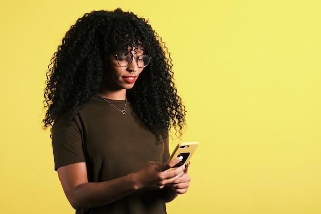 Kędzierzawego włosy afro amerykańska kobieta używa jej telefon komórkowego