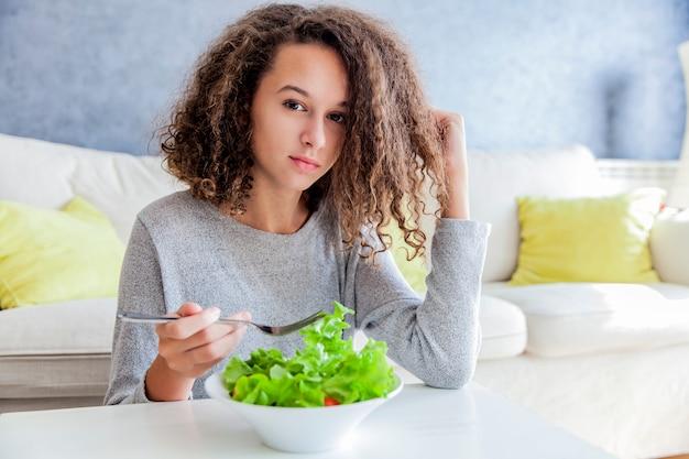 Kędzierzawego włosy nastoletnia dziewczyny łasowania sałatka