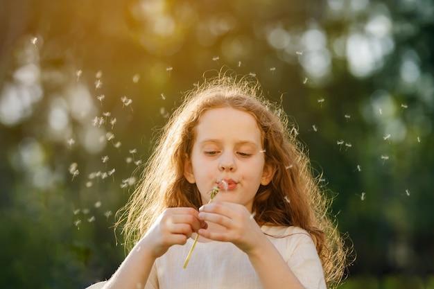 Kędzierzawej dziewczyny podmuchowy dandelion w zmierzchu świetle.