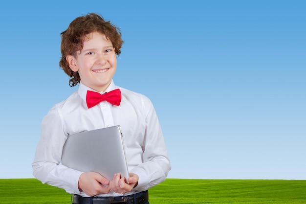 Kędzierzawy chłopiec w formalnym kostiumu z laptopem