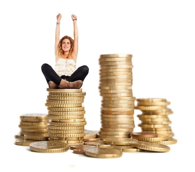 Kędzierzawy kobieta siedzi na stosie monet
