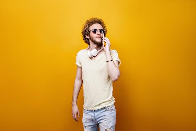 Kędzierzawy mężczyzna w okularach przeciwsłonecznych używa komórkę