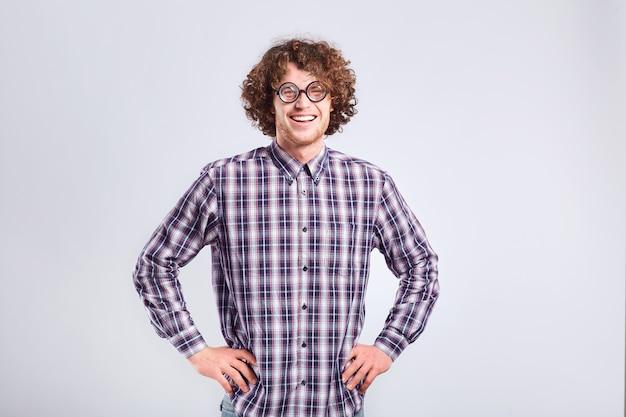 Kędzierzawy nerd mężczyzna w okularach z głupimi zabawnymi emocjami na szarym tle.