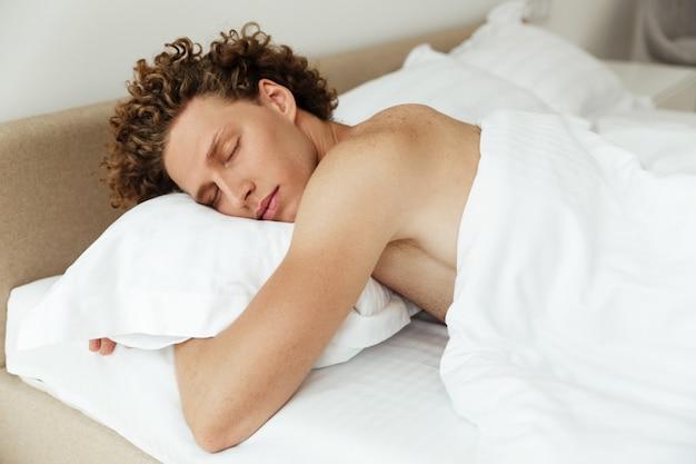 Kędzierzawy przystojny mężczyzna śpi w łóżku w domu