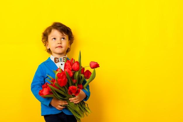 Kędzierzawy śmieszny mały chłopiec w kurtce i muszce z bukietem tulipanów w dłoniach podnosi wzrok