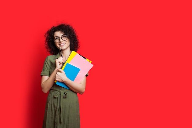 Kędzierzawy student pozuje na czerwonej ścianie z wolną przestrzenią, trzymając kilka książek i długopis
