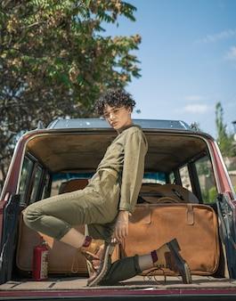Kędzierzawy stylowy model pozuje do zdjęcia z tyłu samochodu w jasny, słoneczny dzień
