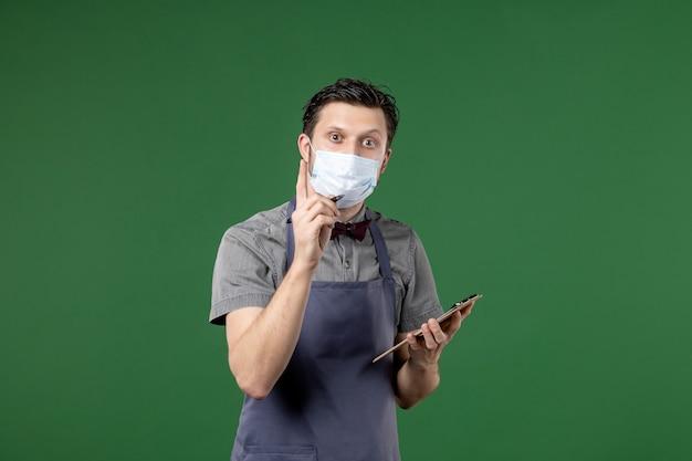 Kelner bankietowy w mundurze z maską medyczną i przyjmujący zamówienie na zielonym tle