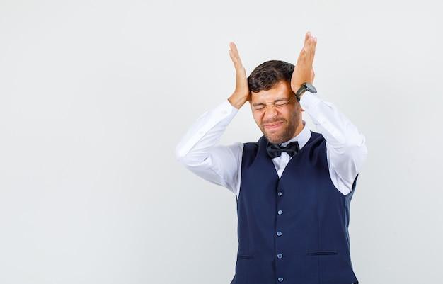 Kelner dotykający skroni dłońmi w koszuli, kamizelce i wyglądający na skruszonego. przedni widok.