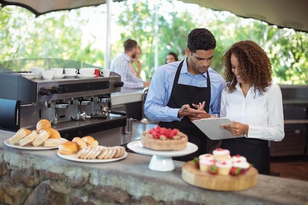Kelner i kelnerka dyskutują w schowku przy kasie