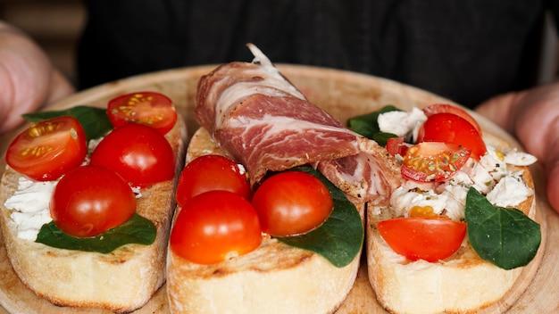 Kelner kobieta trzyma w ręku drewnianą tacę z bruschettą z pomidorkami koktajlowymi. pyszna włoska przystawka