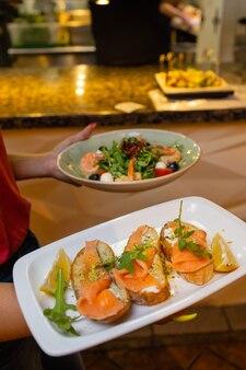 Kelner kobieta trzyma w ręku drewnianą tacę z bruschettą.