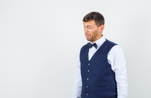 Kelner mrugający okiem w koszuli, kamizelce i śmiesznie wyglądający. przedni widok.