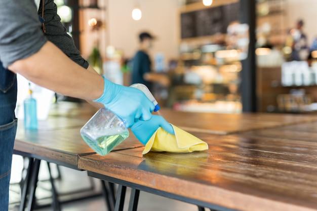 Kelner myje stół sprayem dezynfekującym i ściereczką z mikrofibry w kawiarni.