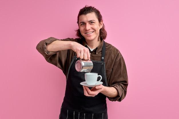 Kelner nalewa pyszną kawę do filiżanki, przystojny facet poleca skosztować takiej kawy w fartuchu