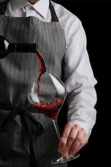 Kelner nalewa wino do kieliszka na ciemnym tle