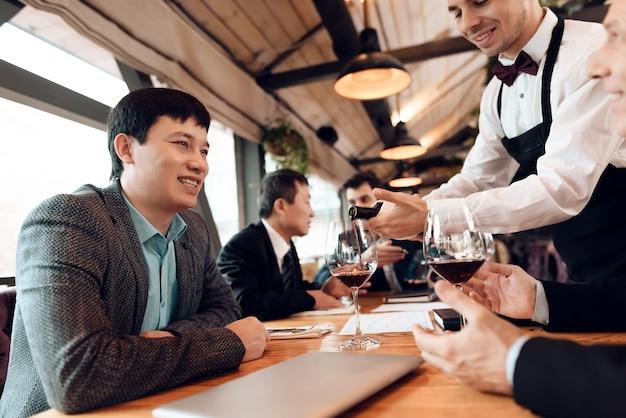 Kelner nalewa wino do szklanek.