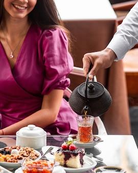 Kelner nalewający kobiecej czarnej herbaty do kieliszka w kształcie gruszki