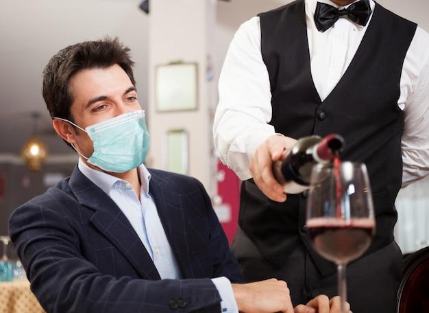 Kelner nalewania wina do zamaskowanego klienta, zabawny koncepcja koronawirusa
