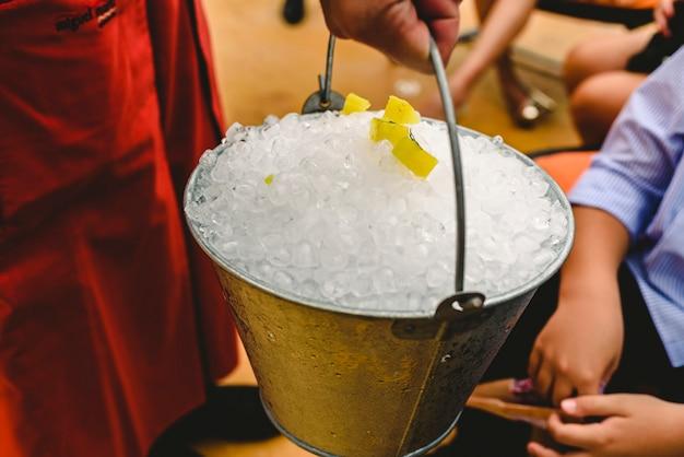 Kelner niosący metalowe wiadro pełne lodu do chłodzenia napojów latem.