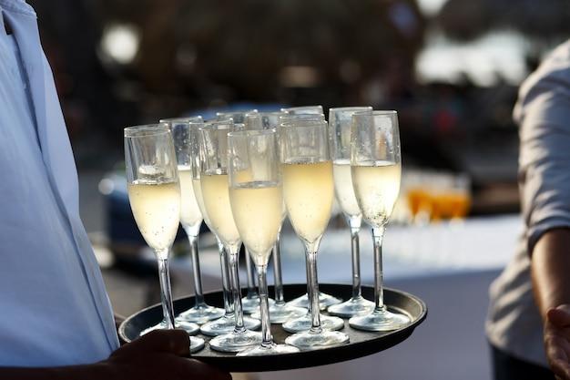 Kelner nosi tacę z szampanem