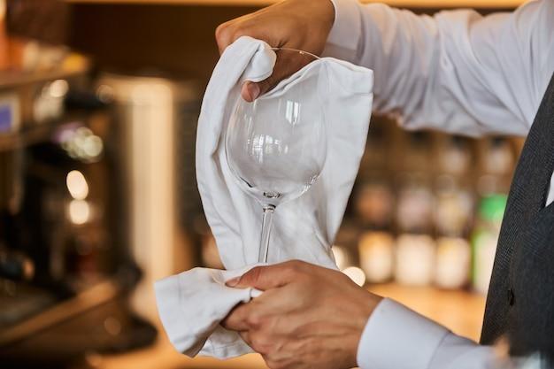 Kelner obsługujący stół. zbliżenie pusty kieliszek do wina, płyta na białym obrusie przed ścianą przerwa.