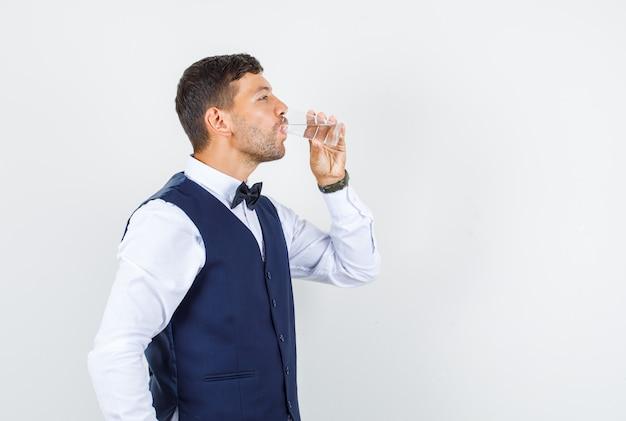 Kelner pije szklankę wody w koszuli, kamizelce i wygląda na spragnionego.