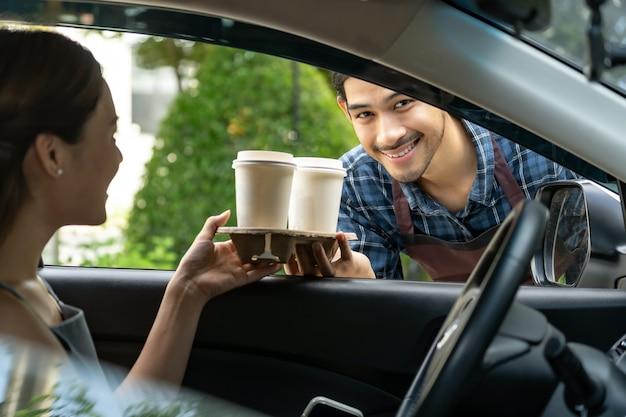 Kelner podający klientowi filiżankę gorącej kawy z jednorazową tacą przez okno samochodu
