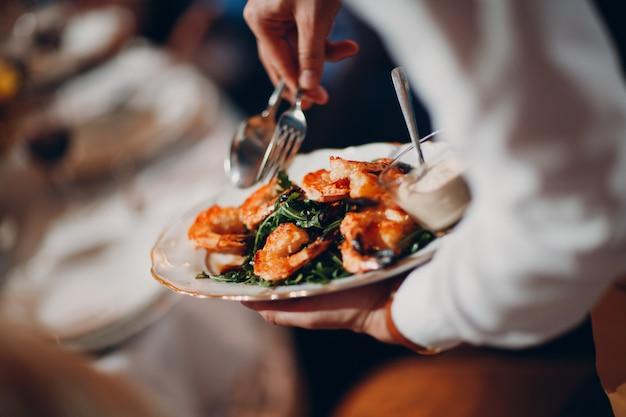 Kelner podaje krewetki z rukolą