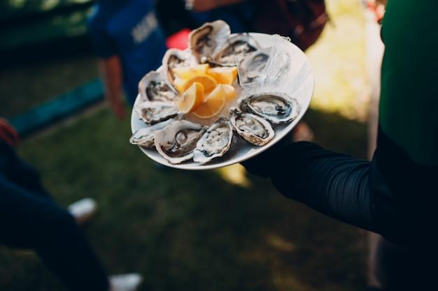 Kelner podaje ostrygi z cytrynami na talerzu. koncepcja gastronomiczna.