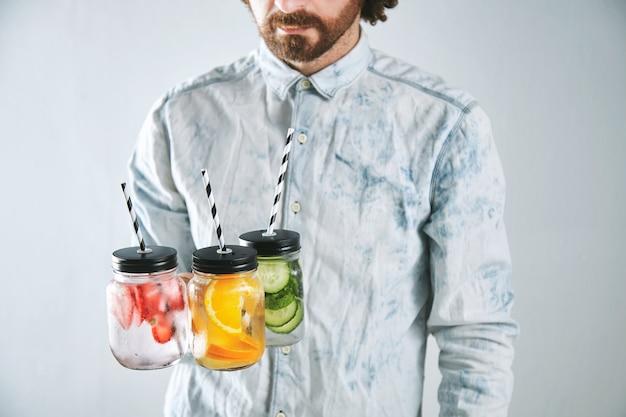 Kelner podaje trzy zimne napoje orzeźwiające z truskawek, pomarańczy, limonki, mięty, ogórka, lodu i wody gazowanej w rustykalnych słoikach ze słomkami w środku
