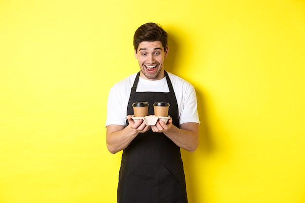 Kelner podekscytowany dwiema filiżankami kawy na wynos, ubrany w czarny fartuch, stojący na żółtym tle.