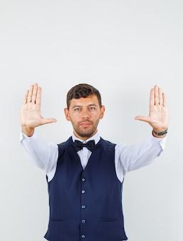 Kelner pokazuje wystarczająco dużo gestów i uśmiecha się w koszuli, widok z przodu kamizelki.